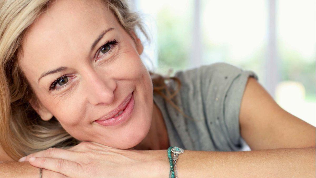 image montrant une femme souriante avec des petites ridules sous les yeux