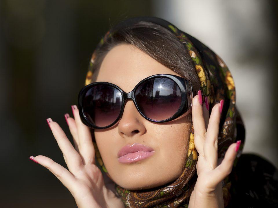 image montrant une femme avec une peau lisse, portant des lunettes de soleil et un foulard dans les cheveux.