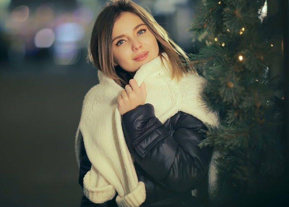 image montrant une femme à l'exterieur souriant avec un pull chaud sur les epaules