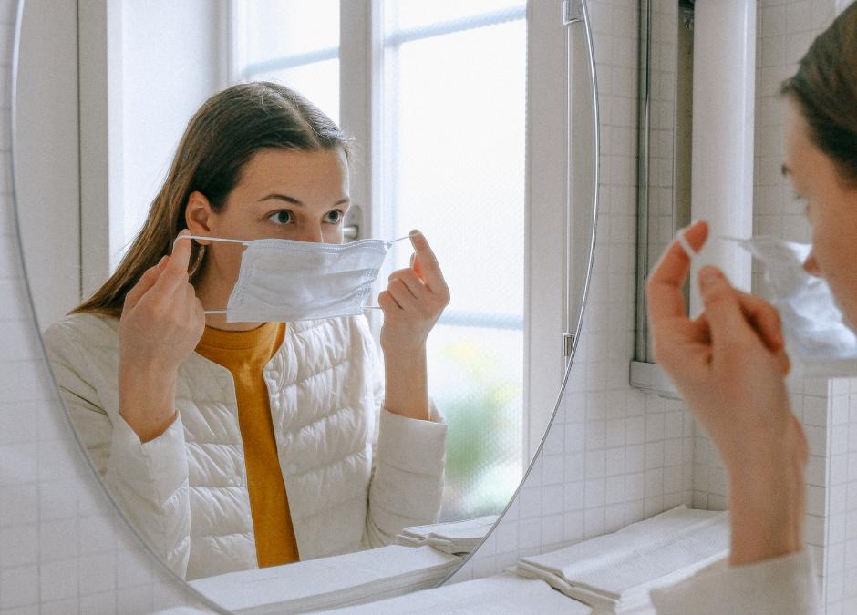 Femme qui met un masque chirurgical sur son visage devant un miroir