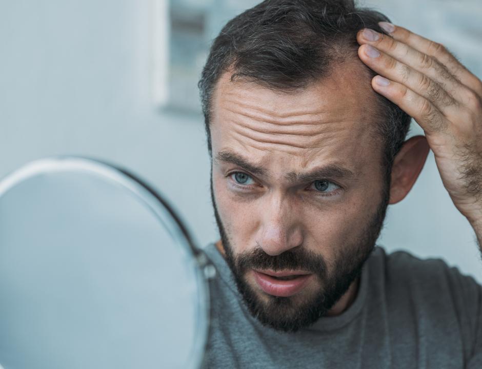 Photo d'un homme qui regarde ses cheveux dans le miroir