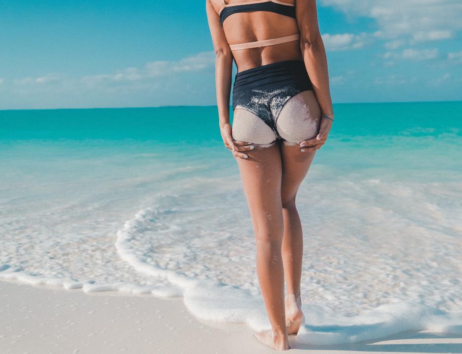 Femme de dos en maillot de bain sur la plage pour illustrer les traitements efficaces contre la cellulite chez Imaderm