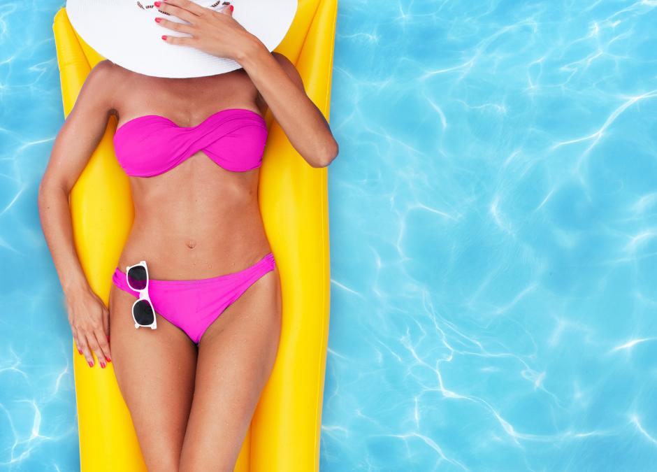 Femme en maillot de bain sur un matelas dans une piscine pour illustrer l'article de blog Imaderm concernant les soins à apporter à sa peau au retour des vacances d'été